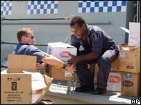 A member of the Australian Navy helps a Solomon Islands' police officer load relief supplies onto a ship in Honiara.