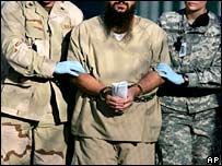 A detainee is led by guards at Guantanamo Bay