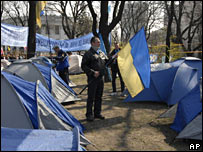 A supporter of Mr Yanukovych holds a national flag in a tent camp in Kiev