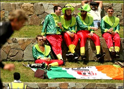 Jacob Oram (L) from New Zealand runs in to bowl as Irish fans (R) look on during the World Cup Cricket Super Eight match against Bangladesh  in St John's .