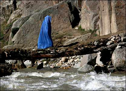 An Afghan woman walks over a foot bridge on her way to home near Sinan village in Zabul province, south-eastern Afghanistan