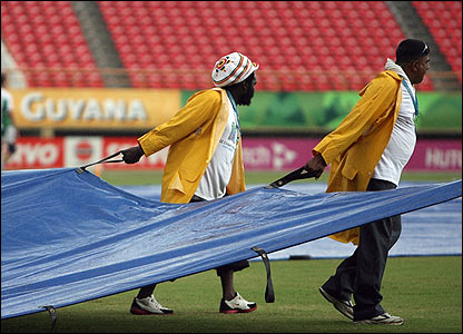 Groundstaff pull the covers onto the square in Guyana