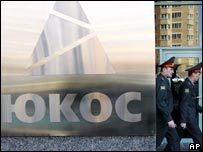 Policemen walking past the Yukos headquarters in Moscow