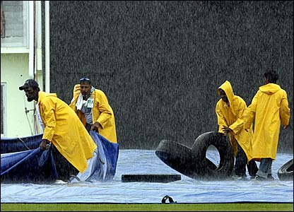 Groundstaff bring the covers back onto the pitch