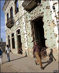 Angolans walking by a building scared by bullet holes dating from the civil war