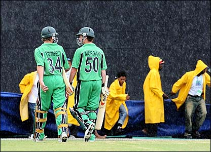 Ireland's William Porterfiled and Eoin Morgan leave the field with rain falling