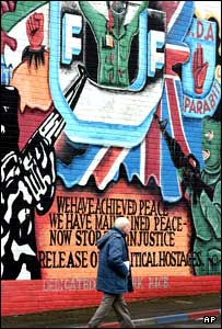 A man walks past a UDA mural in east Belfast