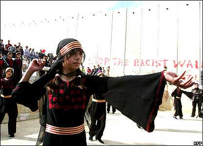 Palestinian girls in traditional costume dance in front of Israel's separation barrier during the Dutch-Palestine Week in the Aida refugee camp close to Bethlehem.