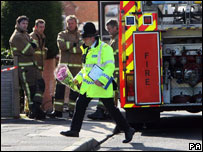 A police officer lays flowers at the scene of the fire