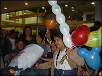 Familia ecuatoriana recibiendo con globos a una pariente que regresa de España
