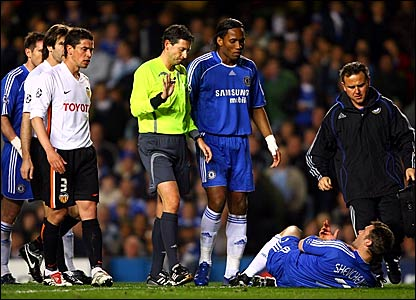 Chelsea's Andriy Shevchenko lies in the penalty area (right) while the referee looks on
