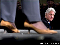 Bill Clinton watches his wife Hillary as she speaks at a fundraising event