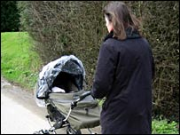 Woman wheels a pushchair in a park