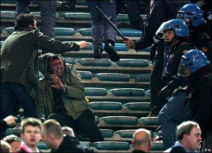 A fan cowers away from an Italian policeman