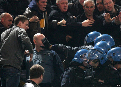 An Italian policeman pushes a fan in the face