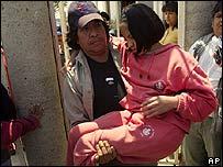 Un padre carga a su hija, una de las estudiantes de la Villa de las Ni�as