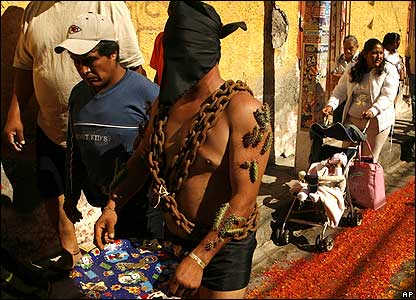 A penitent wearing heavy chains and cactus stuck to his skin takes part in a procession in Mexico.