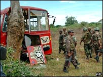 Sri Lankan soldiers by the wreckage of the bus