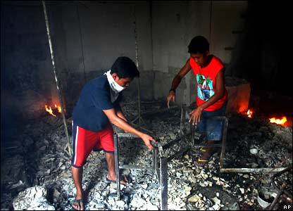 Two boys try to salvage a still smouldering metal frame inside a burned house.