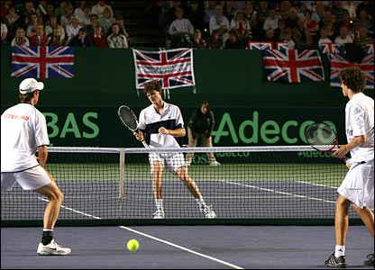 Robin Haase and Roger Wassen look on at Jamie Murray at the net