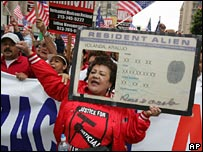 A demonstrator carries a giant resident alien card during the rally