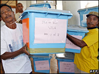 Electoral officials distribute election ballots and boxes in Dili