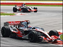Fernando Alonso leads Lewis Hamilton early in the race in Malaysia