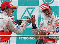 Race winner Fernando Alonso sprays Lewis Hamilton with champagne on the podium
