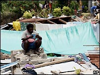 Man sits in rubble of home in Gizo, Solomon Islands