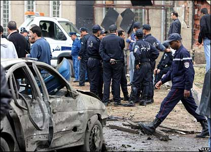 Police walk past a damaged car in front of the Government Palace in the centre of Algiers