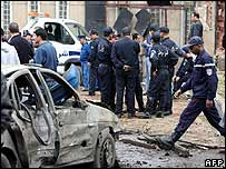 Algerian police pass a damaged car near government buildings in Algiers