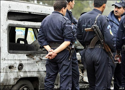 Police stand by blast-damaged cars in Algiers on Wednesday