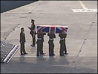 A coffin being carried by pallbearers