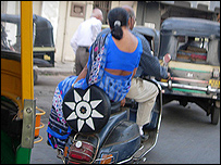 A woman riding side saddle on the back of her husband's moped