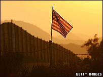 Una bandera de EE.UU. se recorta sobre el muro levantado en la frontera con México