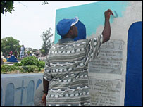 A man paints a gravestone at Palm Grove Cemetery