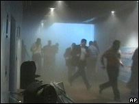 People flee from the smoke-filled parliament building