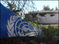UN's blue and white logo lies broken by the gate