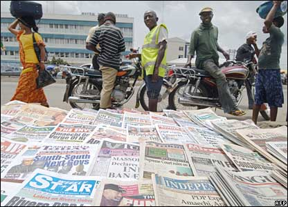 Nigerian pass by a newspaper stand on Thursday