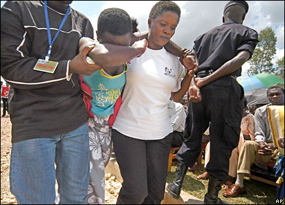 A woman being led away from a Rwandan genocide memorial ceremony