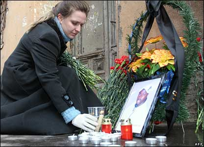 A woman in St Petersburg lights a candle in memory of a murdered Senegalese student