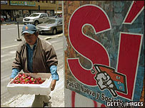 Un comerciante informal al lado de un cartel a favor del Sí