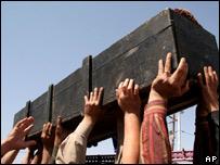 عراقيون يرفعون تابوت أحد ضحايا تفجير انتحاري الأحد في بغداد خلال جنازة في النجف، 12 مارس/آذار 2007