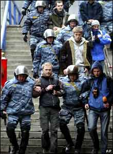 Riot police officers detain a group of journalists during a protest march in Moscow.