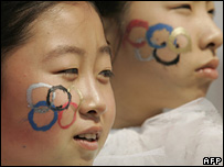 Dancers with Olympic rings painted on their faces at a Beijing ceremony on 13 April
