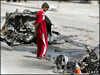 A boy looks at the wreckage of one of the cars used to attack a Baghdad market