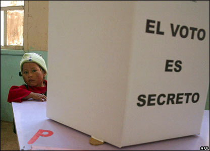 A little boy waits for his mother peering out from behind a voting booth