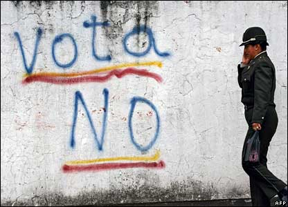 "A policewoman walks past a sign urging people to vote ""No"" in the referendum"