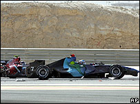 Jenson Button's Honda and Vitantonio Liuzzi's Toro Rosso collide on the first lap of the Bahrain Grand Prix