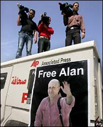 Palestinian cameramen stand on a jeep adorned with a poster of Alan Johnston